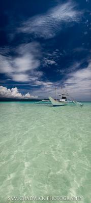 Vertical panorama of boat in clear water in the Phillipines